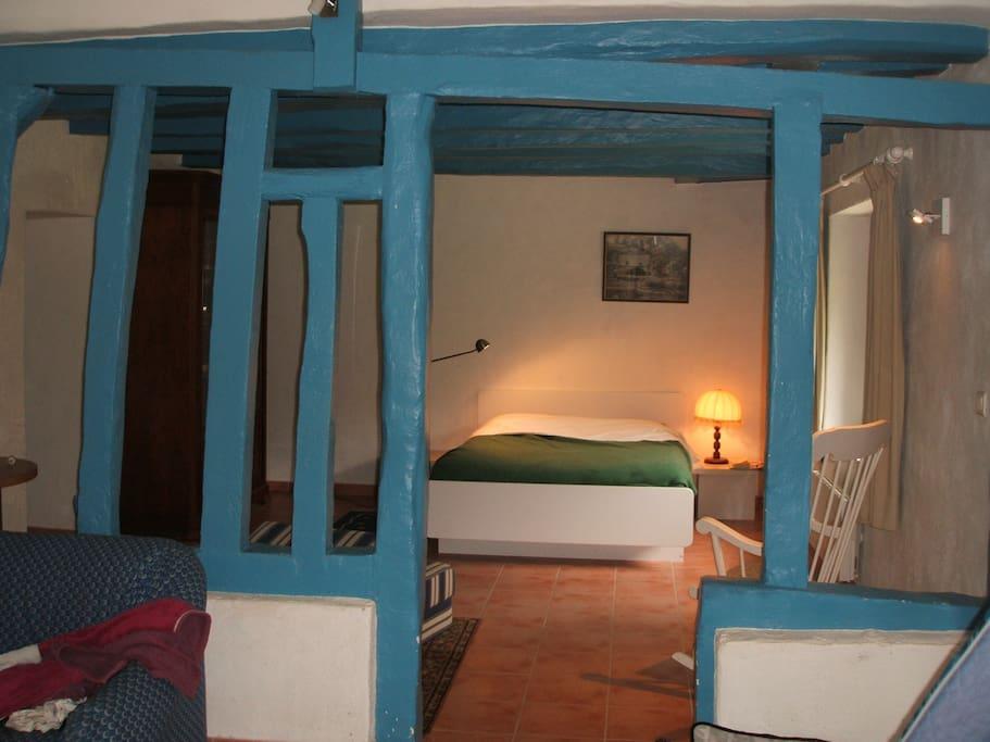 lit double dans la pièce qui communique avec la salle de séjour