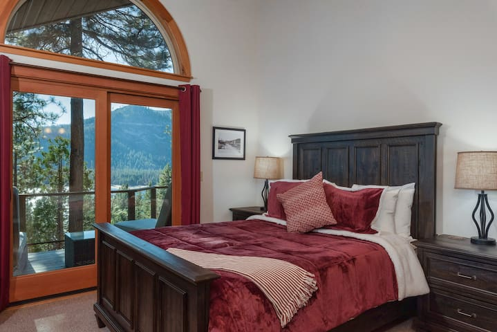 The first-floor master suite features a stately queen  and breathtaking vistas of the mountains.