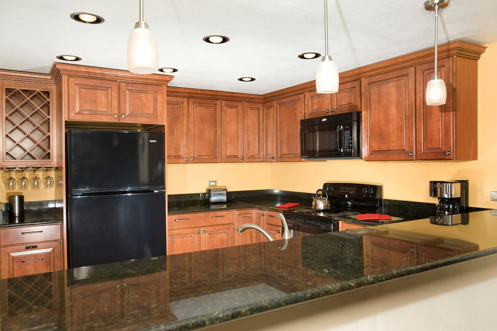 The fully-equipped kitchen features beautiful granite countertops