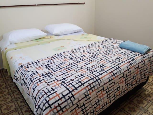Habitación con cama más aire acondicionado y ventilador.