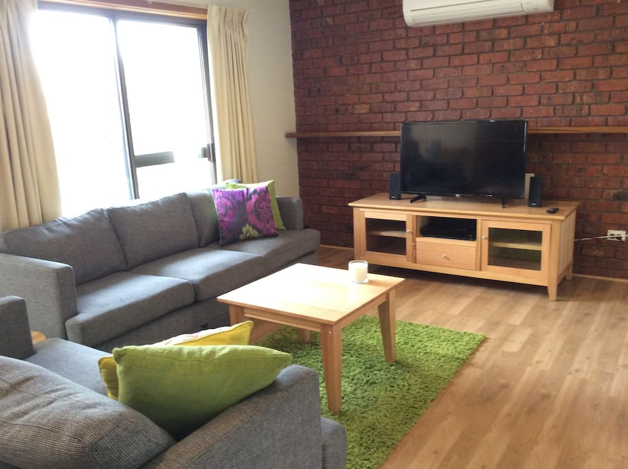 Comfortable sofas on the sunny living room . Flat screen TV