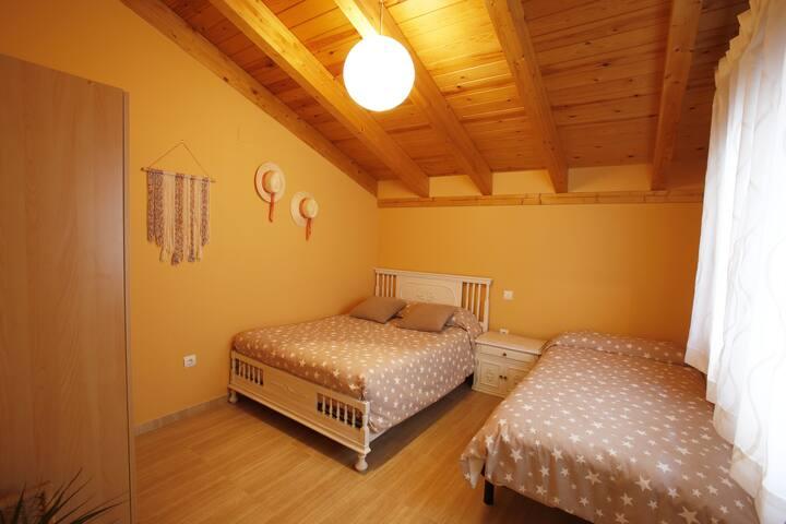 Dormitorio con camas de medidas 1,35 m y 90cm, mesilla y armario. Colchones nuevos. Ropa de cama incluída. Posibilidad de incluir cuna.