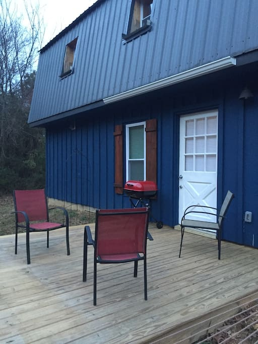 Outside deck with charcoal grill and seating area.