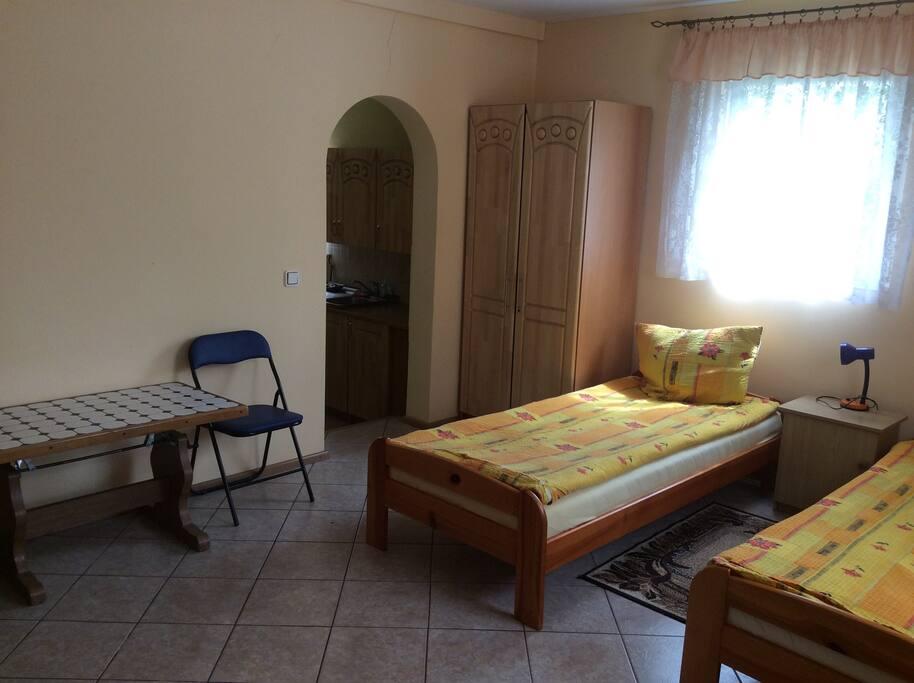 Светлая , уютная комната с двумя кроватями и диваном.