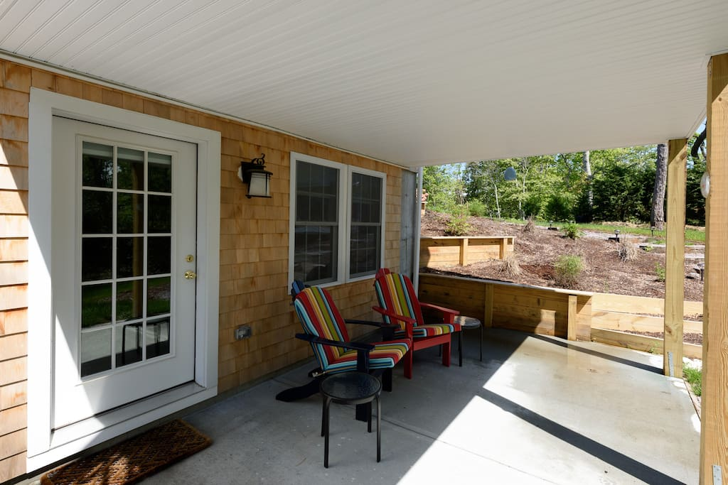 Bright and airy patio with Adirondack cushioned chairs, gas grill and outdoor shower