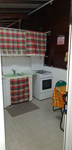 Cuisine équipée avec four, réfrigérateur, micro-onde, vaisselle dont une partie traditionnelle, table intérieur avec 3 chaises, cafetière