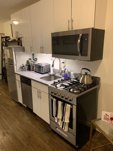 Kitchen with full size refrigerator and freezer, dishwasher, oven, stove top, and mocrowave.