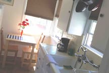 Full Kitchen and dining area with fridge, gas stove, Pots, Microwave, Plates, Dining table, utensils, etc.