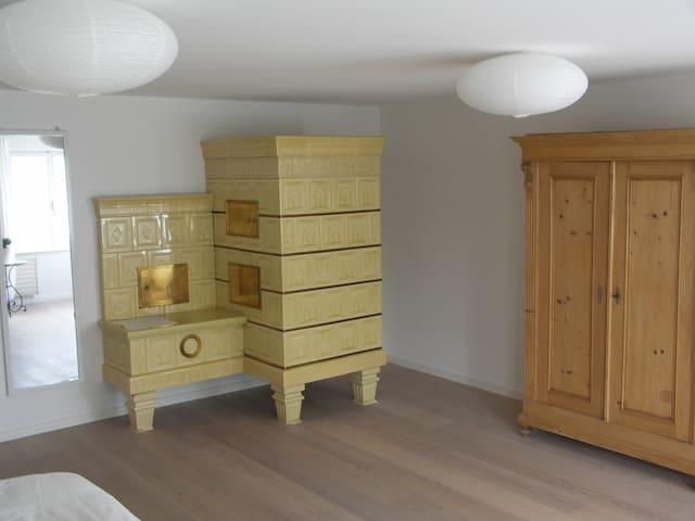 Schlafzimmer mit Kachelofen und Schrank.