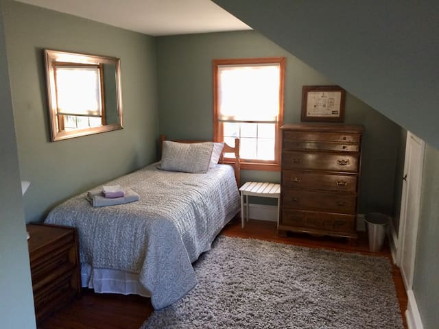 2nd floor bedroom with 2 twin beds next to a bathroom