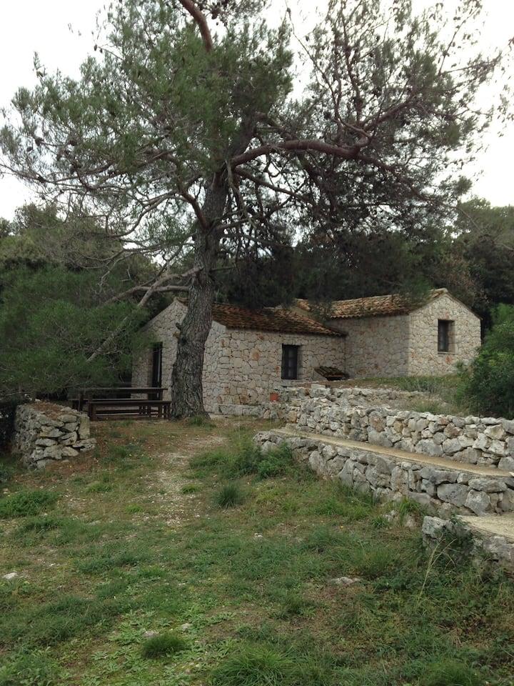 Kamena kuća na malom otoku sa barkom