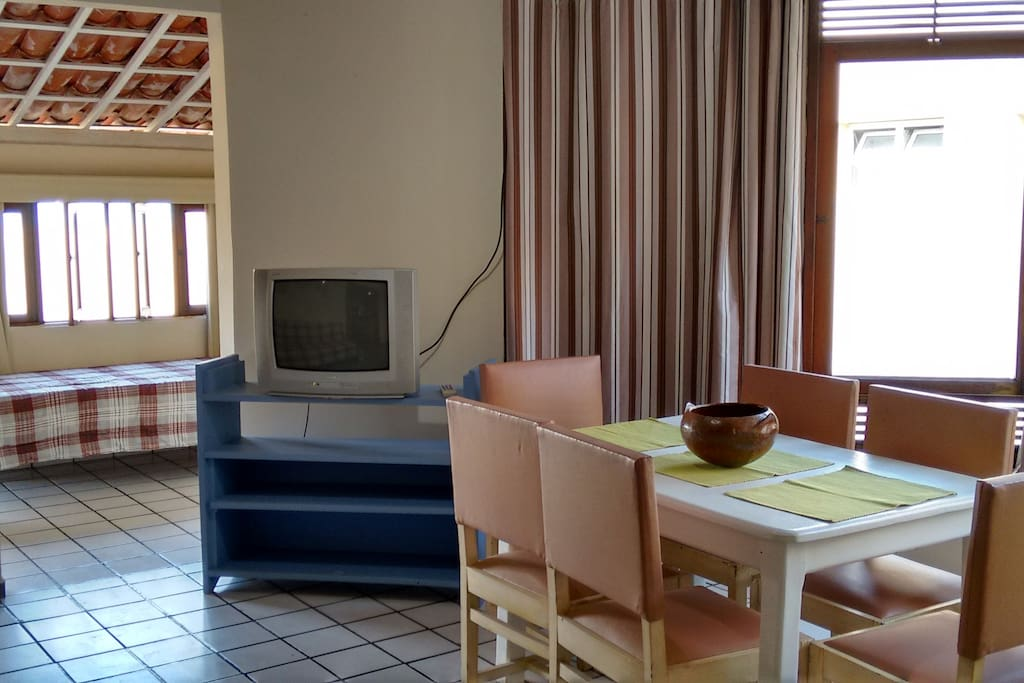 Sala com TV e mesa para refeições