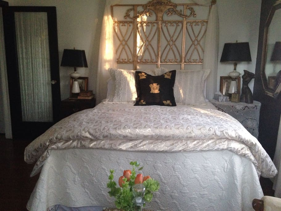 Queen bed dressed in ivory and golds