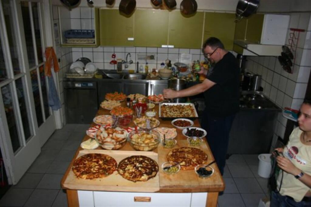 Die voll ausgestattete Küche liegt direkt neben dem Essraum. Auf dem Großküchenherd kann man für viele Personen kochen. Mit der Großküchenspülmaschine ist der Abwasch schnell erledigt. Geschirr und Kochgeräte sind natürlich vorhanden.