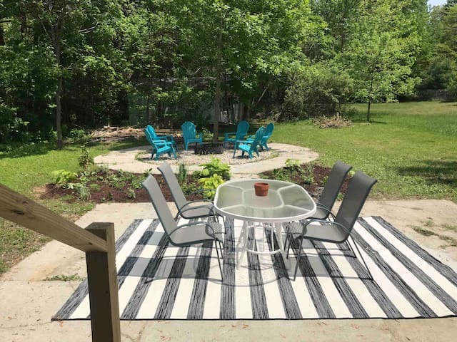 Couple steps down to patio, large gas grill, fire pit, dining table, and outdoor shower and hose for sandy feet