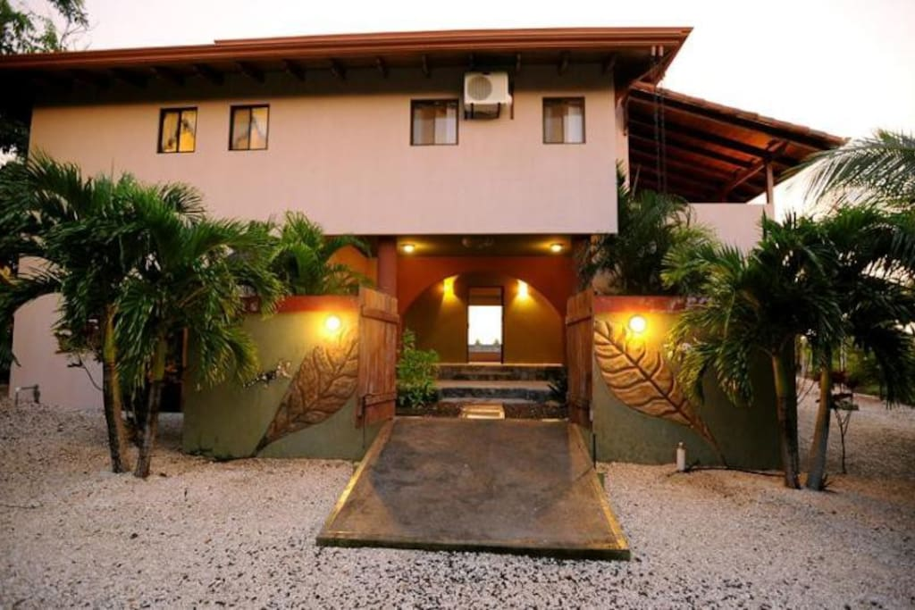 Front of house welcomes you with garden entry, laundry, outdoor shower and stairs to main living area