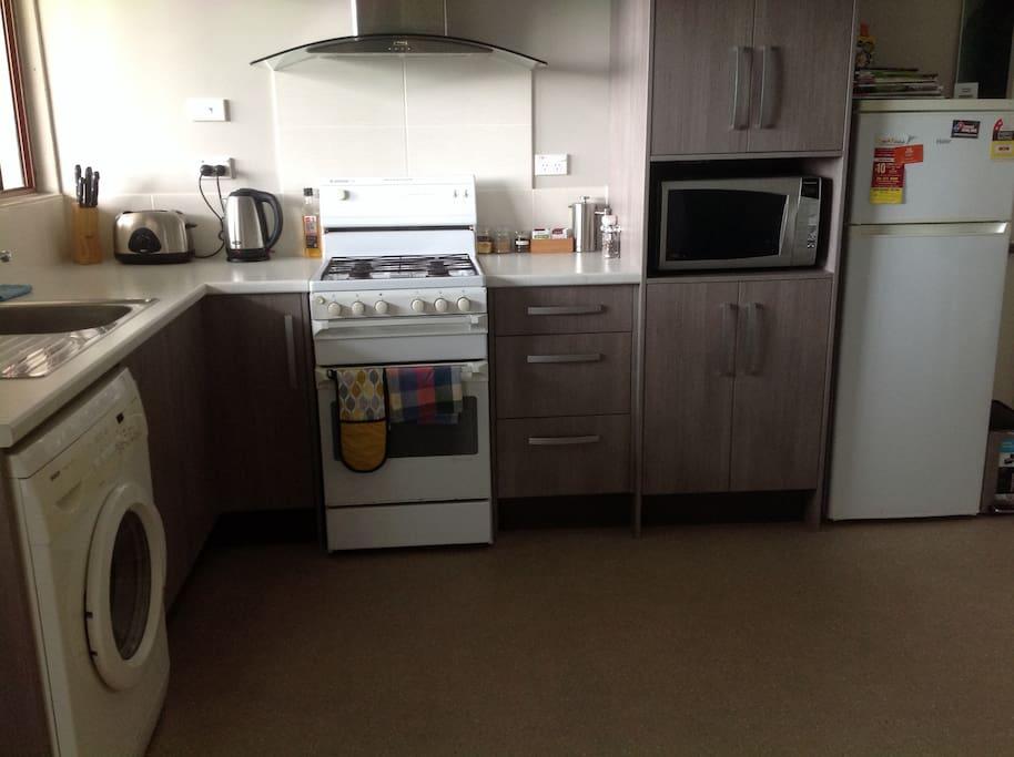 Full size kitchen with Oven, Fridge/Freezer and Washing Machine.