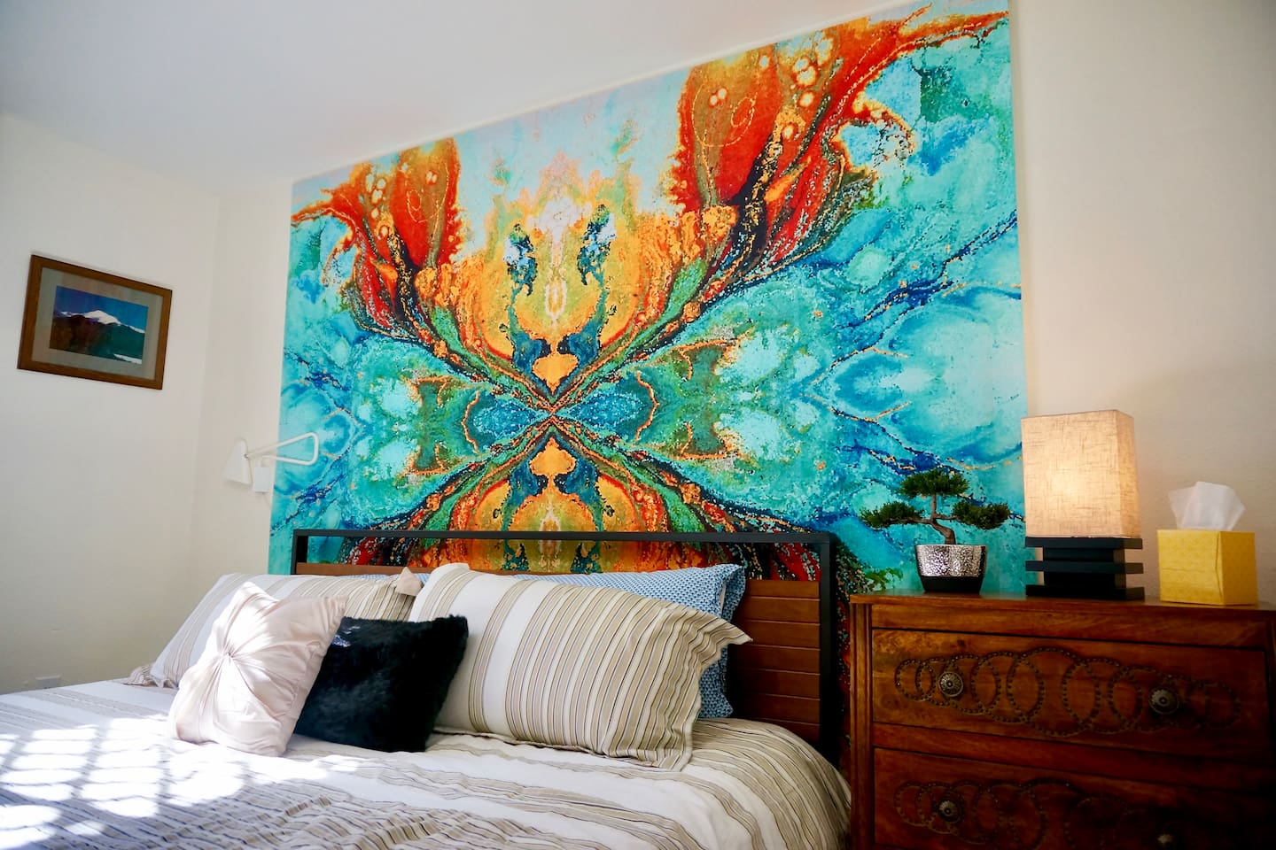 King size bed in a spacious room. Vibrant mural to start and end your day.
