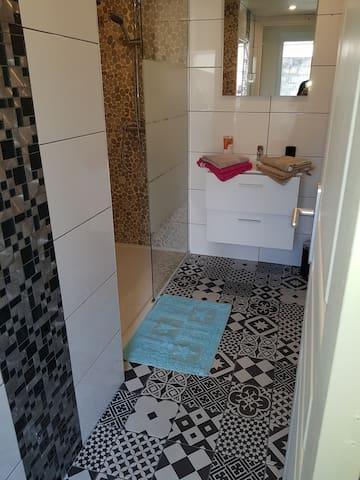Salle de bain avec lavabo, miroir, radiateur sèche serviette et douche italienne.