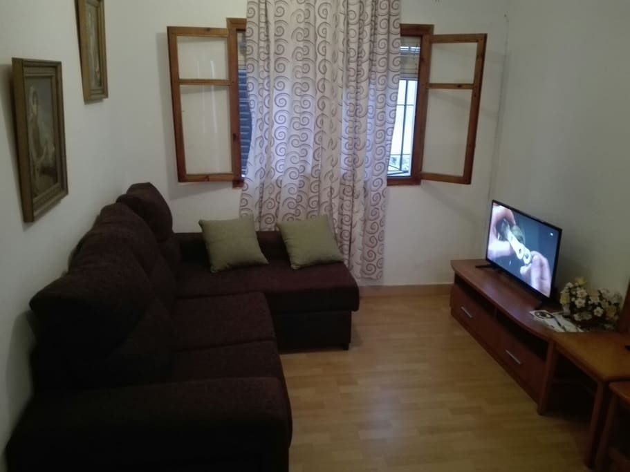 Salón con un cómodo sofá Cheiselonge y TV.