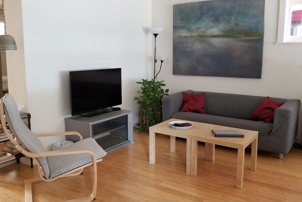Bright living room with flatscreen tv featuring Netflix and access to AppleTV, and a radio/ CD player.