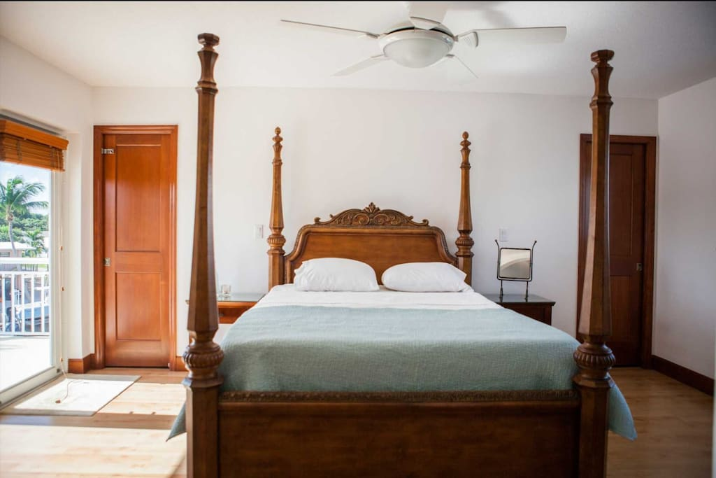 Master Suite bedroom with a queen bed, his & hers closets, third floor balcony access with pool and waterway views