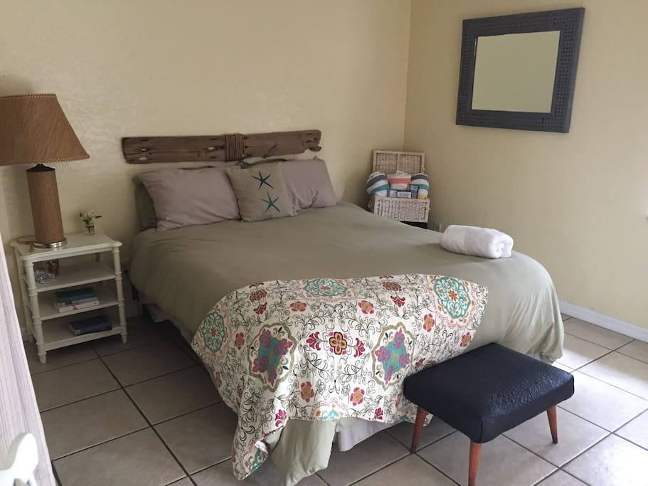 Main Guest Bedroom- Queen bed, basket with local brochures, and beach towels