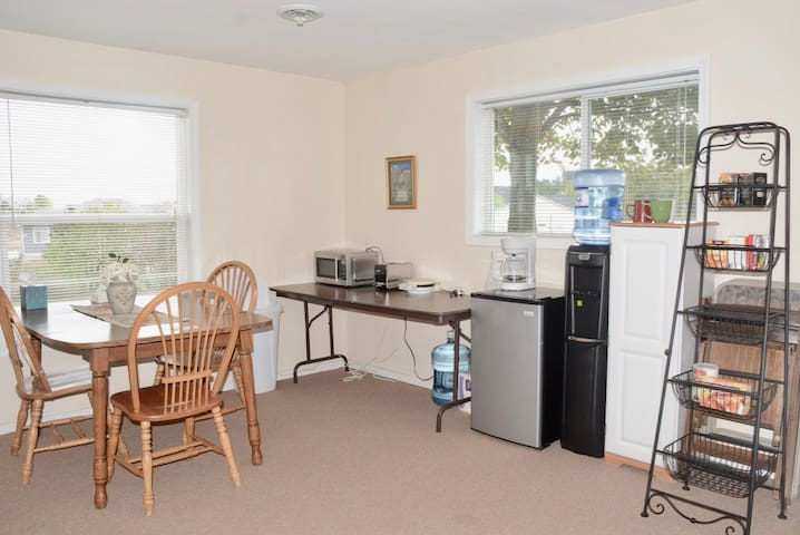 Kitchenette with fridge, microwave, toaster, coffee maker, water cooler, and breakfast foods provided.