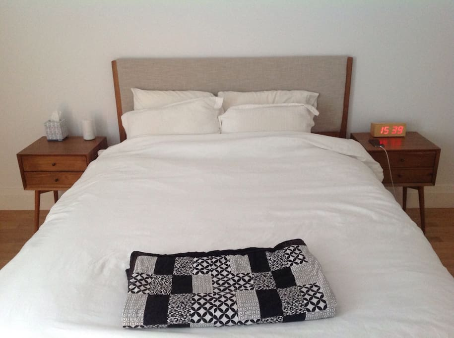 Comfortable queen bed (Casper mattress), close to power outlets for easy charging.