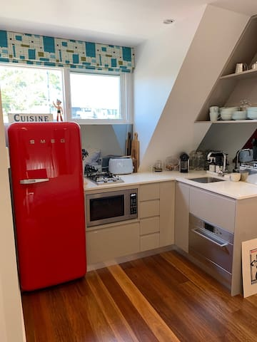 Small functional kitchen including 2-burner gas stove, microwave, fridge, freezer, dishwasher and Nespresso Machine.
