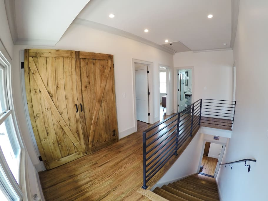 Wide angle of the entrance to the suite. Laundry is located behind barn doors; the bedroom doorways are to the left, and the bathroom is straight down the hallway.