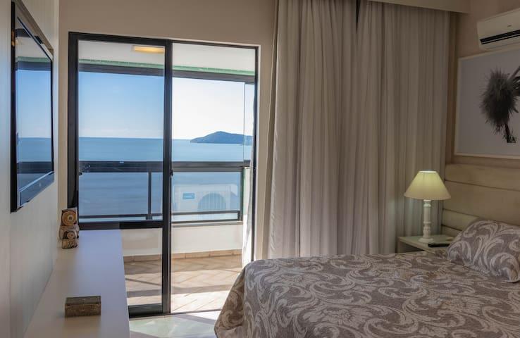 Suite 1 com sacada e vista para o mar.