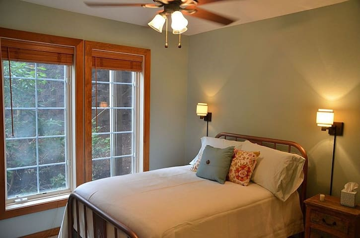 Guest bedroom with queen bed and large windows.