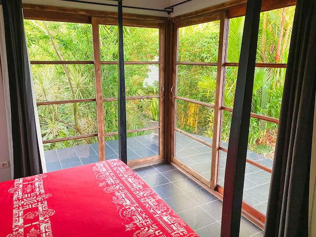 The main bedroom overlooking the lush garden. A relaxing space to rest, read and cuddle.