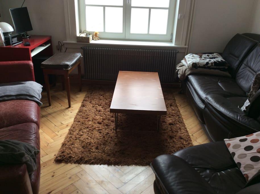 Petit salon avec deux canapés et un fauteuil