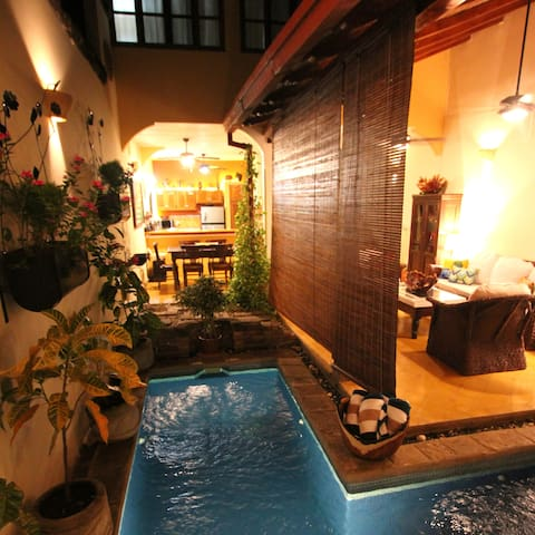 Additional view of pool at night with shade down (dining / kitchen in background, master bedroom window above, downstairs bedroom directly behind). Wall sconces throughout the house give a warm and cozy feel during tropical evenings