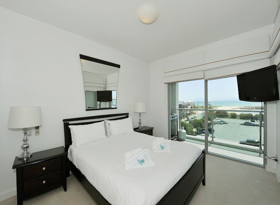Main Bedroom with queen size bed overlooking the ocean. The main bedroom has it's own Television.