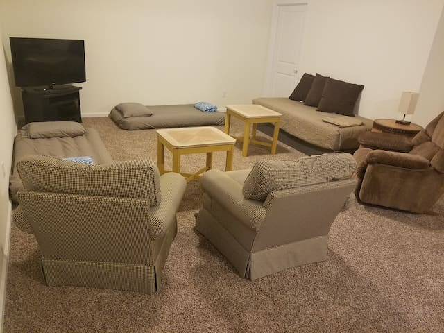 Large smart TV, comfortable seating and twin bed with two air mattresses visible in the TV nook.