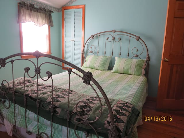 Upstairs third bedroom with a Queen bed with a peak at the ocean.