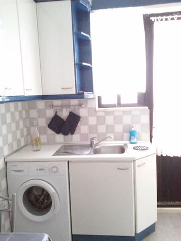 Washing machine in the kitchen. Access to the rear balcony.