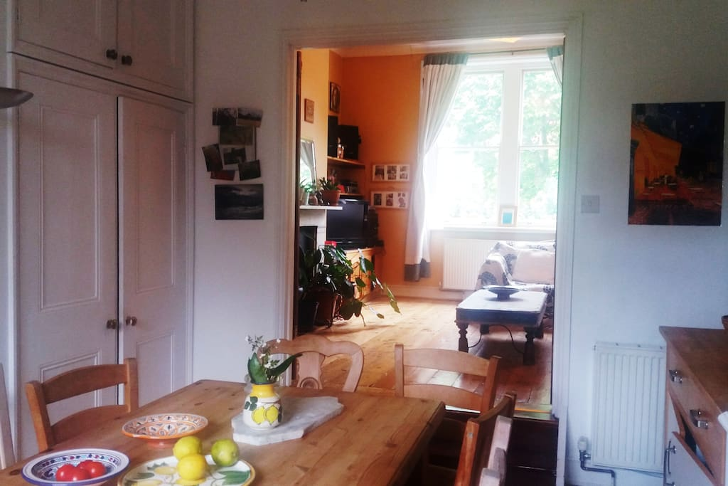 Very large fully equipped family kitchen with pine table looking into the living room.