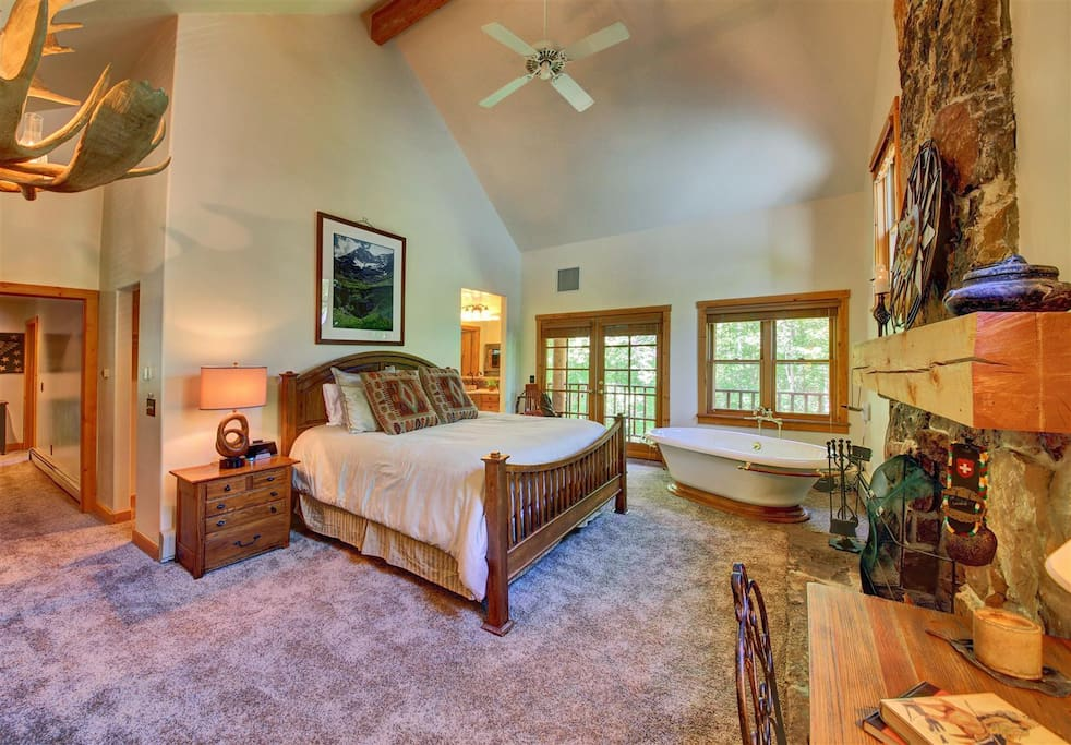 Master bedroom on upper level with full bath, private deck, wood burning fireplace and vaulted ceilings