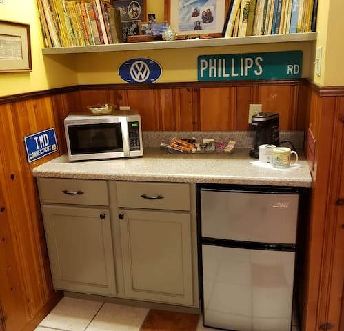 Mini kitchen area includes fridg with freezer, microwave, coffee maker, and snacks.