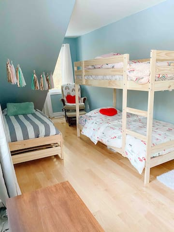 This room is located right across from the master. It has twin bunk beds, and a set of stacking twins (that can be either two singles (twins) or strapped together creating a double). Here you'll also find the children's reading nook w/ rocking chair.
