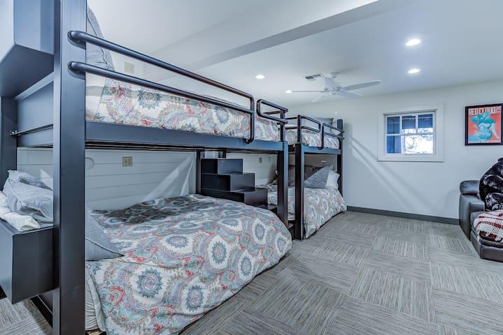 The basement bedroom offers custom bunk beds containing 4 queen beds.