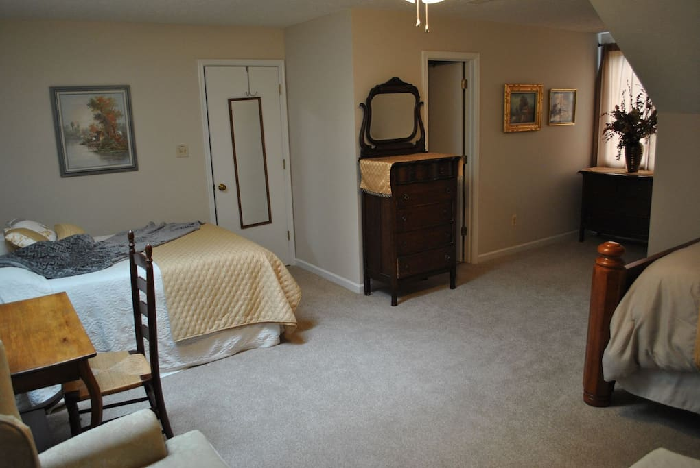 The on-suite is to the right of the chest of drawers.