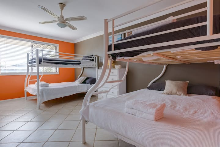 The spacious fourth bedroom features two sets of bunk beds, both with double beds on the bottom and single beds on top. This room accommodates six guests in total, ideal for those travelling in large groups.