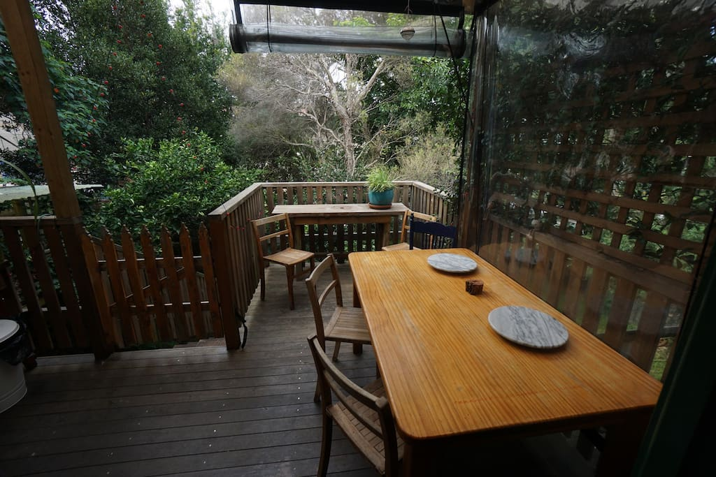 Double leadlight doors lead to shared outside covered deck overlooking leafy back garden.