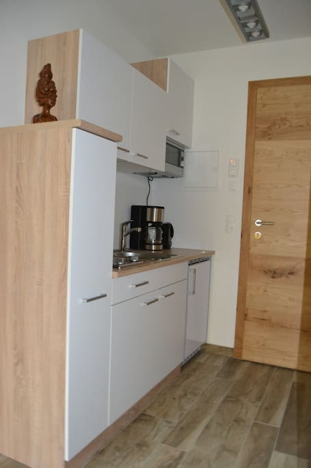 Well-equiped kitchen corner with stove-top, microwave, fridge and dining and cooking gear