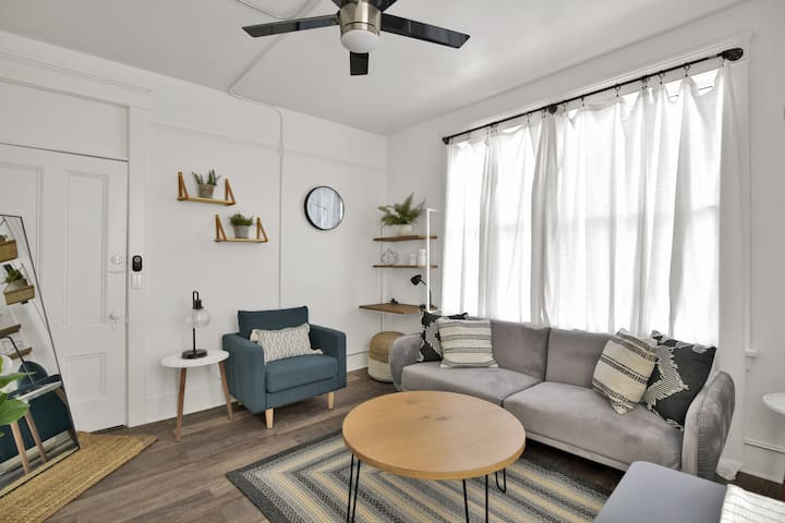 Main living area with the comfy sofa chair to cozy up with a coffee and a book and futon! There is also a small desk space and table and stools for two.